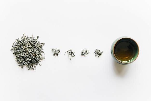 Dried tea herb with teacup isolated on white backdrop