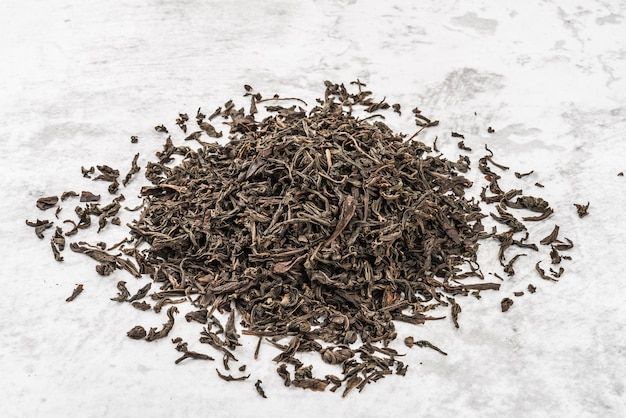 Dried tea is piled on a marble table.