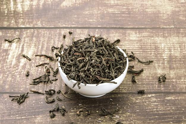 乾燥したお茶は、木の板のテーブルの上のセラミックカップに注がれます。