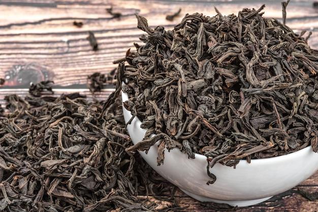 Высушенный чай наливают в керамическую чашку на деревянном дощатом столе.
