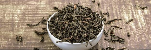 乾燥茶は木の板テーブルの上のセラミックカップに注がれる