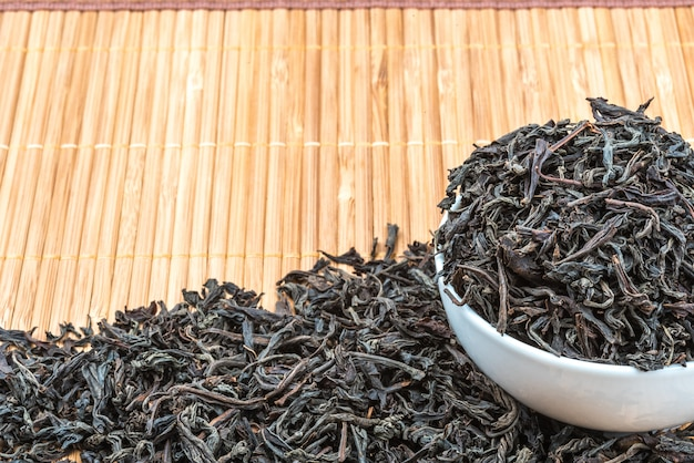 Dried tea is poured into a ceramic cup on a bamboo mat.