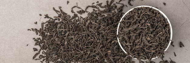 Dried tea is poured into a white ceramic cup on a gray textured background. view from above. layout.