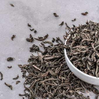 Dried tea is poured into a white ceramic cup on a gray textured background.