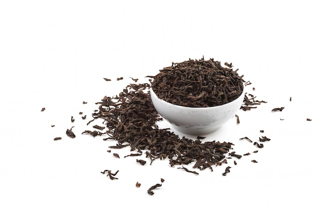 Dried tea leaves in ceramic cup over white background.