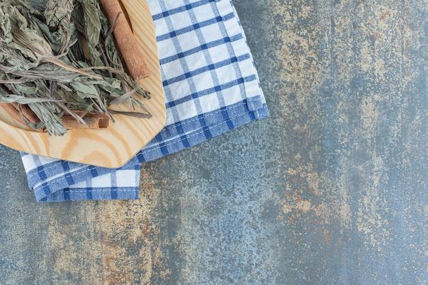 Foglie di tè essiccate e bastoncini di cannella sul piatto di legno.
