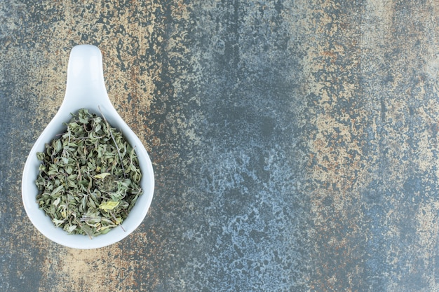 Dried tea leaves in white bowl.
