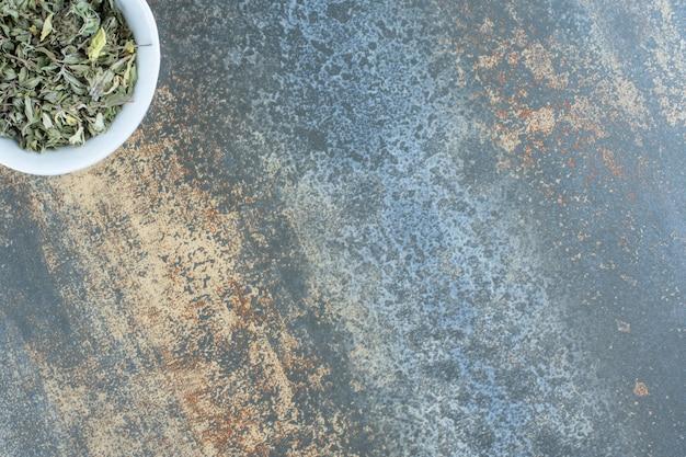 Foglie di tè essiccate in una ciotola bianca.