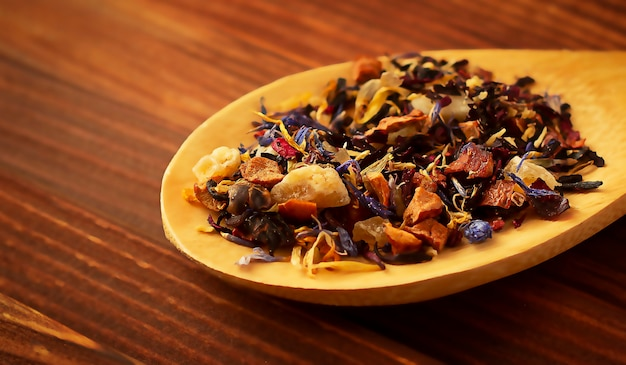 Dried tea leaves in a wooden spoon on a wooden table