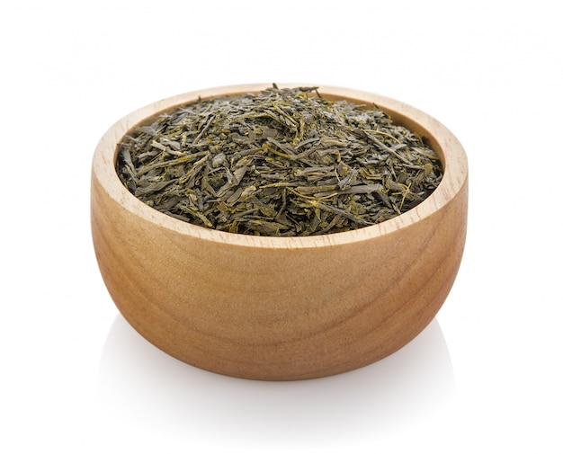 Dried tea in wood bowl on white space