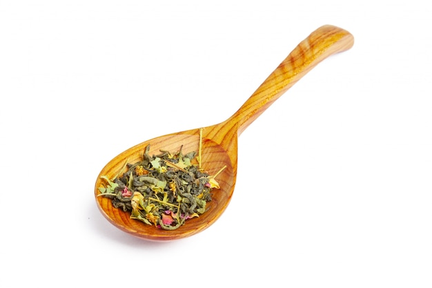 Dried tea on a wooden spoon, isolated on white