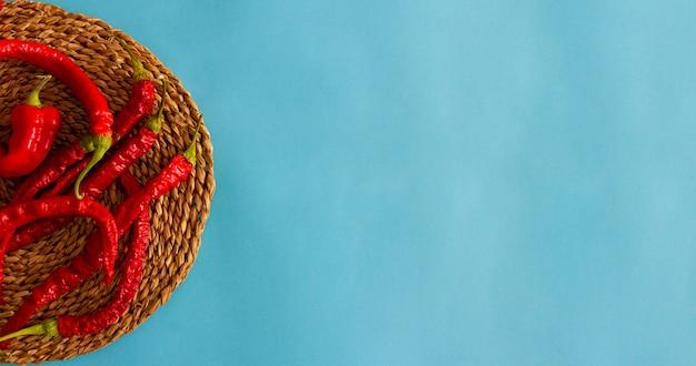 青い背景の枝編み細工品トレイに乾燥した薄い赤唐辛子。上面図。フラットレイ。スペースをコピーします。