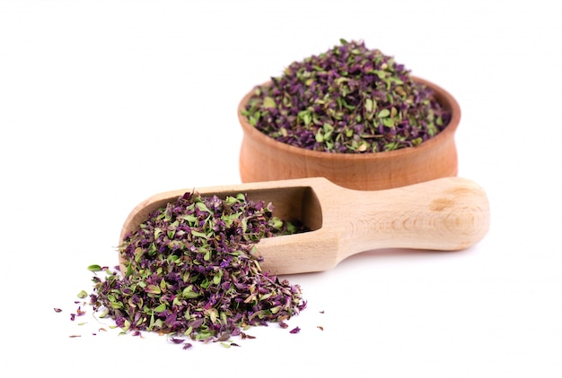Dried thyme flowers in wooden bowl, isolated