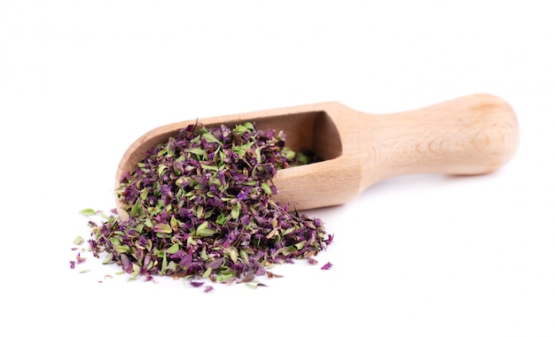 Dried thyme flowers in wooden spoon