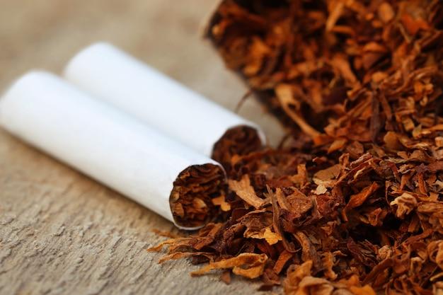Сушеные табачные листья с сигаретой на деревянной поверхности