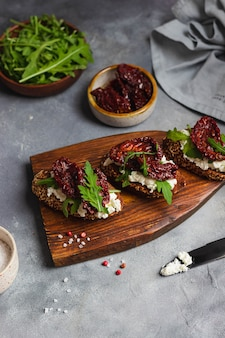 Dried tomato bruschetta with cottage cheese, garlic, arugula, whole grain bread and olive oil served on a gray stone backgroundwith blue linen napkin and black knife. top view.