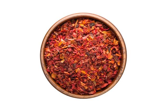 白い背景で隔離の木製ボウルに乾燥トマトパウダースパイス。調味料上面図