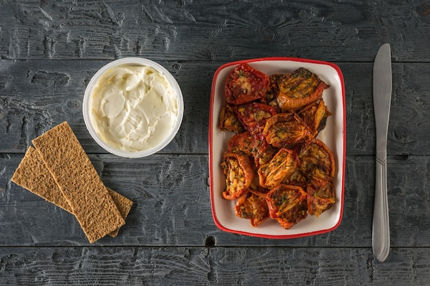 Dried tomatoes with cream cheese and a knife on a wooden table. mediterranean tomato appetizer. vegetarian food. flat lay.