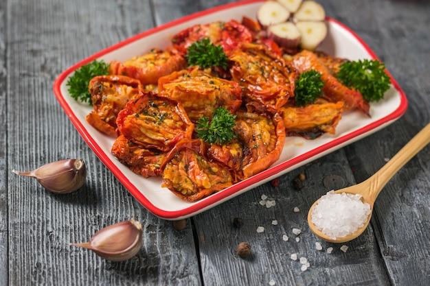 Сушеные помидоры с чесноком и ложкой с крупной солью на деревянном столе. средиземноморская закуска из томатов. вегетарианская еда.