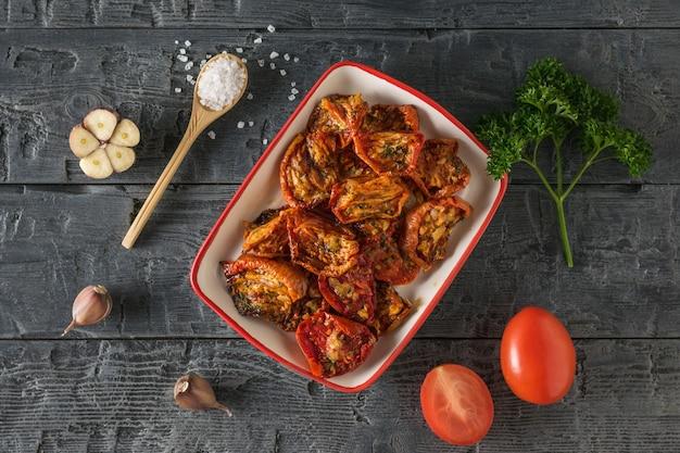 Сушеные помидоры с чесноком и петрушкой на деревянном столе. средиземноморская закуска из томатов. вегетарианская пища.