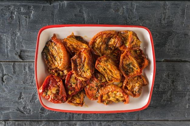 Сушеные помидоры с чесноком и перцем в оливковом масле в тарелке на деревянном столе. средиземноморская закуска из томатов. вегетарианская пища. вид сверху.