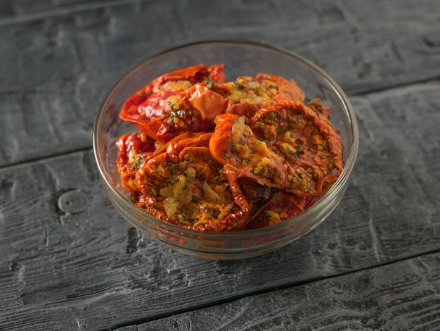Dried tomatoes with garlic in a glass bowl on a wooden table. mediterranean tomato appetizer. vegetarian food.