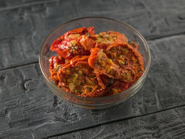 Сушеные помидоры с чесноком в стеклянной миске на деревянном столе. средиземноморская закуска из томатов. вегетарианская еда.