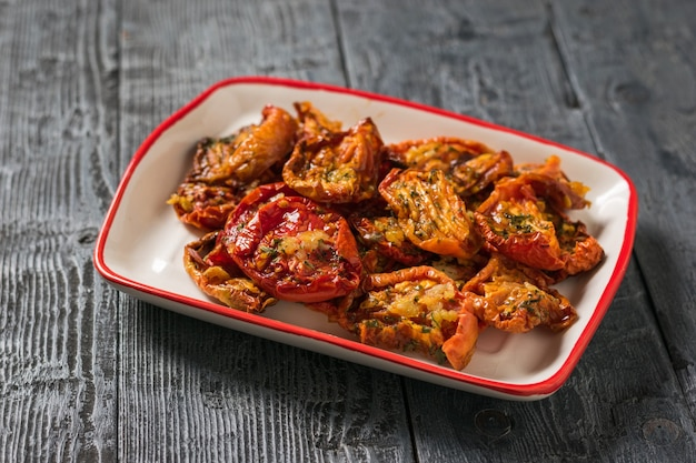 Dried tomatoes with garlic and pepper in olive oil in a plate on a wooden table. mediterranean tomato appetizer. vegetarian food.