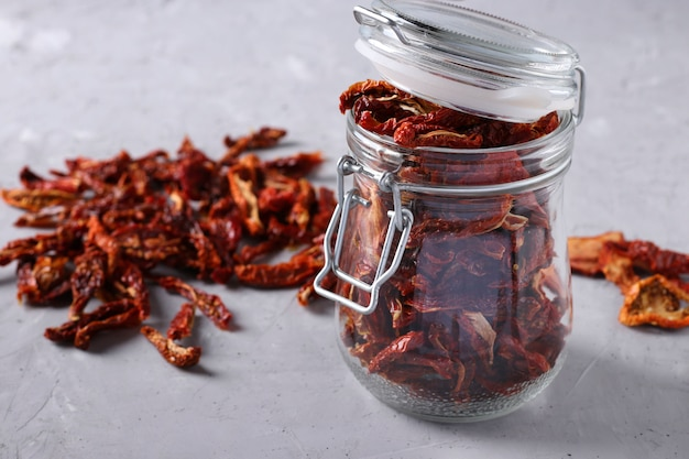 Dried tomatoes with a glass jar on a gray concrete table. horizontal format