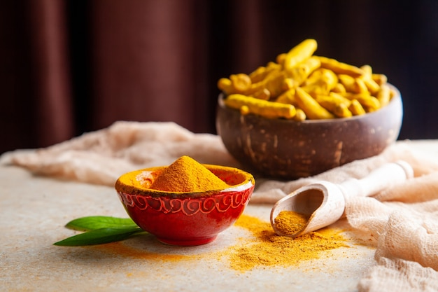 ココナッツの殻のボウルに葉と根が入った乾燥ウコン粉末。
