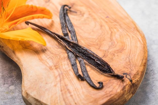 Сушеные палочки ванили и цветок орхидеи ванили на деревянном столе крупным планом