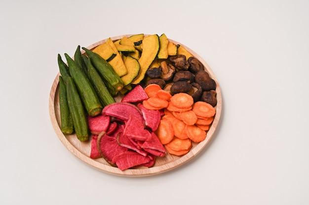 乾燥野菜のチップスにオクラ、ニンジン、カボチャ、ビートルート、椎茸を木製トレイに載せたもの。