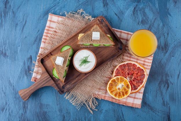 ジュースのグラスの横にある乾燥野菜、サンドイッチ、黄麻布ナプキンのボード、青。
