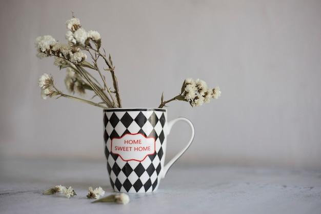 홈 스위트 홈이라는 문구가 있는 회색 배경 컵에 흑백 컵에 말린 흰색 꽃