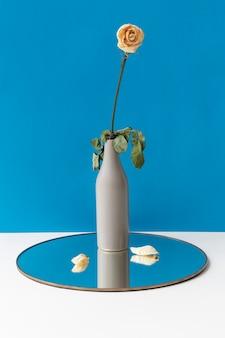 빛나는 둥근 쟁반에 꽃병에 말린 흰 장미