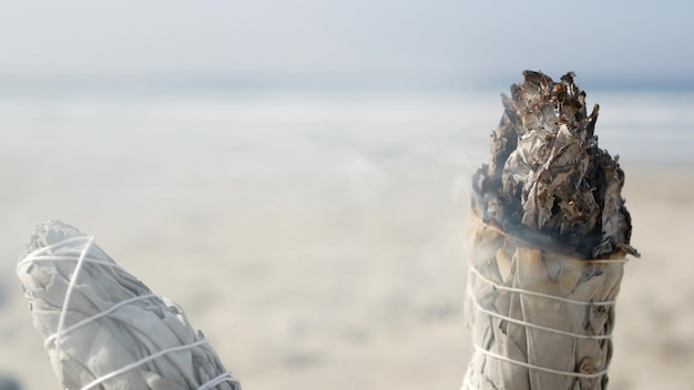 Дым сушеного белого шалфея, горит сухая мазь. размытие аромата на берегу океана