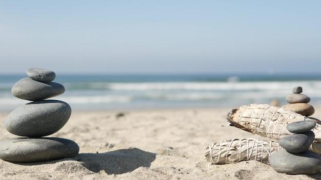 말린 화이트 세이지, 스머지 스틱 굽기, 아로마 스 머징. 오션 비치, 자갈 돌에 균형 바위