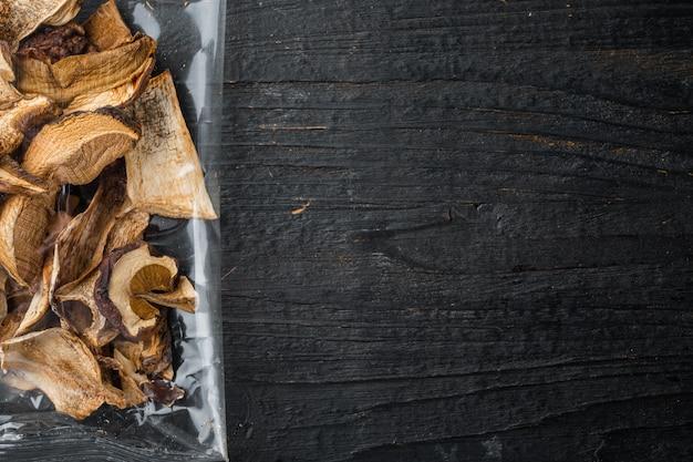 검은색 나무 테이블 배경에 있는 말린 야생 버섯 세트, 플라스틱 팩, 위쪽 뷰 플랫 레이, 텍스트 카피스페이스 공간