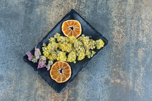 乾燥した黄色い花とオレンジ色のスライスを黒いプレートに。