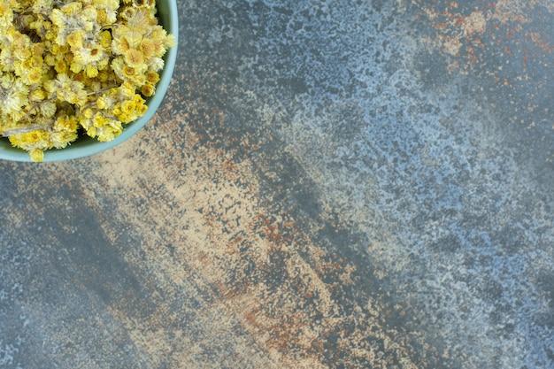 Fiori gialli secchi in ciotola blu.