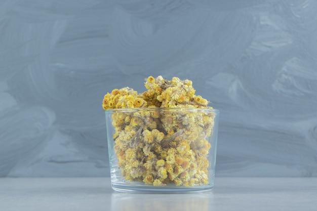 Fiori gialli secchi in tazza di vetro.