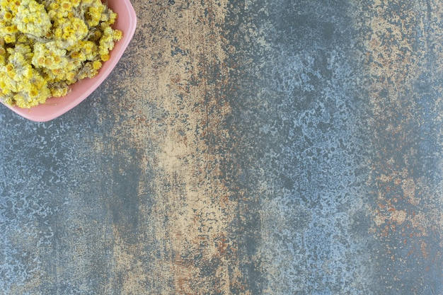 분홍색 그릇에 말린 노란 꽃.