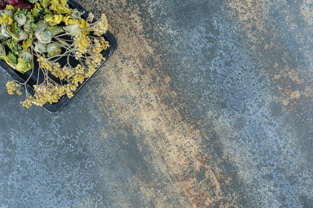 暗いプレートに黄色い花を乾燥させた。