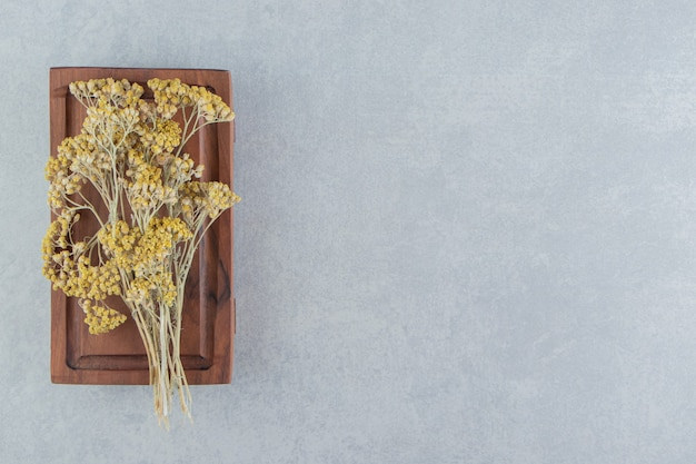 Dried yellow flowers on wooden board.