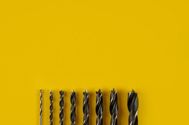 黄色に分離されたさまざまなサイズのドリルビット