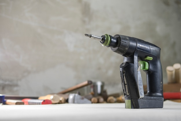 Drill screwdriver in the carpentry mater on the workbench