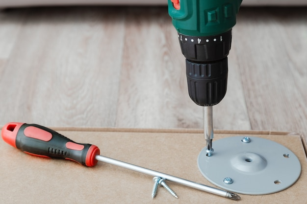 Drill screwdriver and screw. furniture desk table assembling. professional renovation home tools for carpentry and wood diy.