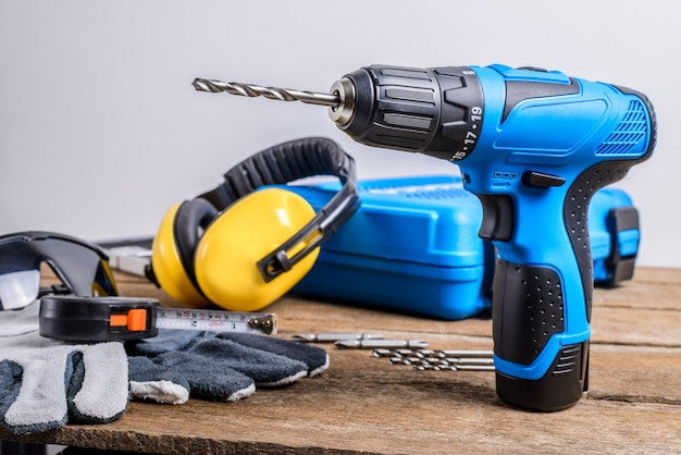 Drill and set of drill, tools, carpenter and safety, protection equipment