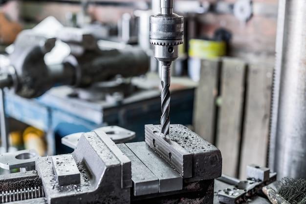 드릴링 머신. 드릴 비트는 드릴 척에 설치됩니다. 기계 바이스, 금속 가공 공장.