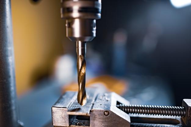 부스러기가 클로즈업된 드릴링 프로세스, 공구맨 자물쇠 제조공의 작업장에서 드릴링 머신